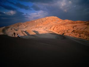 Couple of Hikers Walking Through Shadows at Dusk, Valle De La Luna, Chile by Aaron McCoy