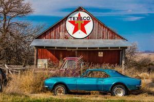 Abandoned blue Camaro Chevrolete in front of deserted Texaco Station, remote part of Nebraska