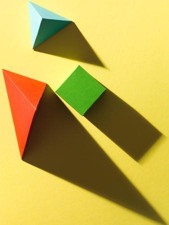 Paper Cube and Pyramids with Harsh Shadow on Yellow Background