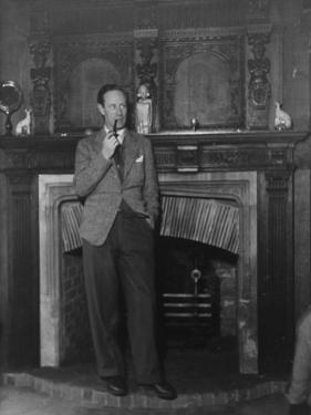 Actor Leslie Howard Smoking Pipe as He Stands by His Fireplace, at Home in Dorking, England
