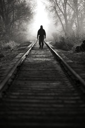 A Male Angler Walks Down Train Tracks Near the Middle Provo River in Winter in Utah