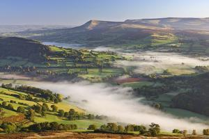 Mist covered rolling countryside backed by the Black Mountains, Brecon Beacons National Park, Powys by Adam Burton