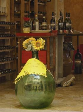 Sunflowers in front of small wine shop, Tuscany, Pienza, Italy by Adam Jones