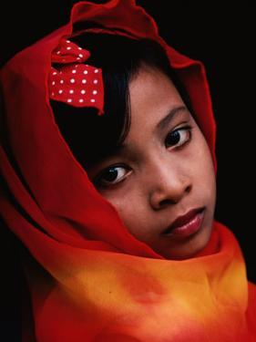 A Portrait of a Muslim Girl with Her Face Framed by a Colourful Scarf, Indonesia by Adams Gregory