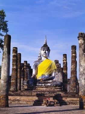 Statue of the Buddha with Religious Offerings, Wat Mahathat, Sukothai, Thailand by Adina Tovy