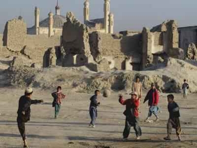 Afghan Boys Play Soccer Near a Mosque and Ruined Buildings During the Early Morning