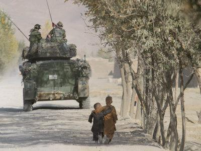 https://imgc.allpostersimages.com/img/posters/afghan-boys-walk-along-a-path-while-international-security-assistance-force-isaf_u-L-Q10OPXJ0.jpg?p=0