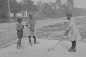 African American Children Pretend to Play Golf on Country Road