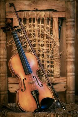 Left Handled Violin Lying on an Old and Ruined Chair by AGCuesta