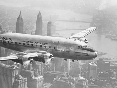 https://imgc.allpostersimages.com/img/posters/aircraft-flying-over-city_u-L-PZOGP80.jpg?p=0