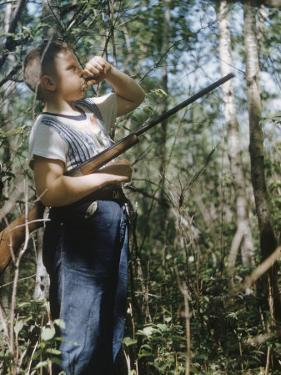 Young Hunter Blowing a Duck Decal Wistle while Holding His Rifle under His Arm by Al Fenn