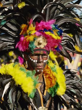 Man with Facial Decoration and Head-Dress with Feathers at Mardi Gras Carnival, Philippines by Alain Evrard