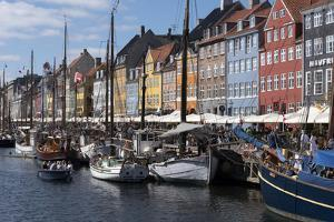 Denmark, Copenhagen, Nyhavn district. Colorful 17th and 18th century buildings, boats and canal by Alan Klehr