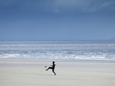 Brazil, Maranhao, Sao Luis, Sao Marcos Beach, Boy Playing Football on the Beach by Alex Robinson