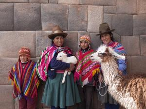 South America, Peru, Cusco. Quechua People in Front of An Inca Wall, Holding a Lamb and a Llama by Alex Robinson