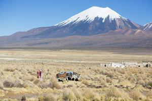 A Farmer Crosses a Landscape Below a Volcano in Sajama National Park by Alex Saberi
