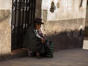 A Traditional Bolivian Woman Sits on a Doorstep in Potosi at Sunset by Alex Saberi