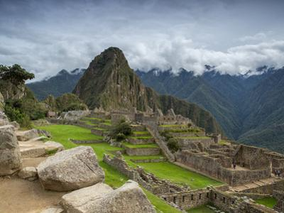 A wide angle photo of Macchu Pichu at sunrise with dramatic clouds in the distance. by Alex Saberi
