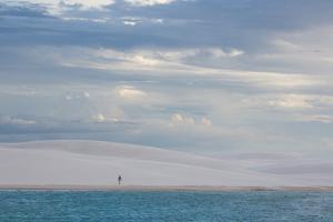 A Woman Walks across the Dunes in Brazil's Lencois Maranhenses National Park by Alex Saberi