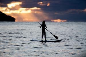 A Young Girl on a Stand Up Paddle Board on Baleia Beach at Sunset by Alex Saberi
