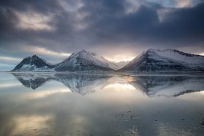 Reflection of mountains on ocean at sunset in Vatnajokull National Park in eastern Iceland by Alex Saberi