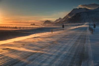 Snow Blows across an Icelandic Road at Sunrise with Mountains Looming in the Distance