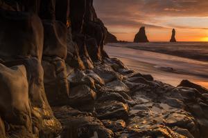 The basalt rock formations in the sea on Reynisfjara Beach in Vik, Iceland at sunrise. by Alex Saberi