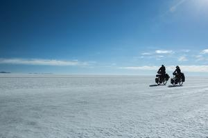 Two Cyclists Cycle in the Morning over the Salar De Uyuni by Alex Saberi
