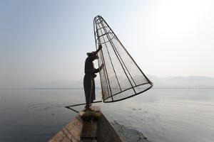 A Basket Fisherman on Inle Lake Prepares to Plunge a Cone Shaped Net by Alex Treadway