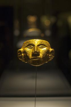 A Gold Mask in a Display Case at the Gold Museum in Bogota, Colombia by Alex Treadway