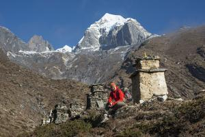 A Hiker Sits Below Tabochhe on the Trail to Everest Base Camp Sits by a Row of Chortens by Alex Treadway
