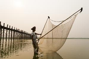 A Man Fishes Next the U Bein Bridge in Mandalay Region by Alex Treadway