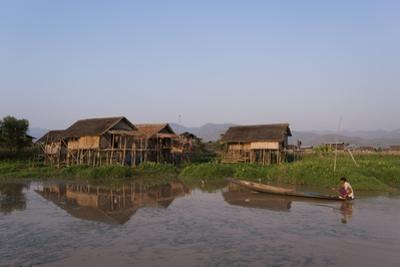 A man paddles his canoe past one of the floating villages on Inle Lake, Myanmar (Burma), Asia by Alex Treadway