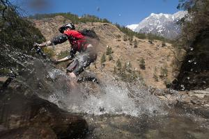 A Mountain Biker Blasts Through a Stream in the Mountains of Nepal by Alex Treadway