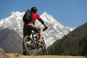 A Mountain Biker in the Tsum Valley Looks at Ganesh Himal Mountains by Alex Treadway
