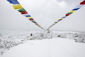 A Porter Walks by a Puja with Prayer Flag in Everest Base Camp, Nepal by Alex Treadway