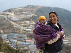 A Woman Carries Her Baby in a Blanket with Namche Visible Behind by Alex Treadway