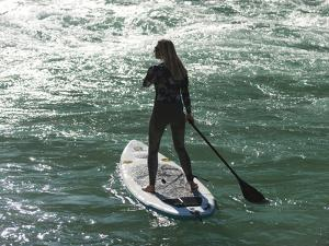A Woman on a Stand Up Paddleboard on the Karnali River in Nepal by Alex Treadway