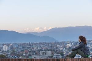 A Woman Sits on a Rooftop in Kathmandu and with the Ganesh Himal Mountain Range in the Distance by Alex Treadway