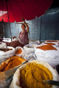 A Woman Weighing Spices on a Market Stall by Alex Treadway