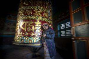 An Old Tibetan Woman Spins a Prayer Wheel While Counting Through a String of Rosary Beads by Alex Treadway