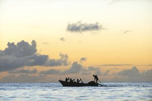 Seine fisherman lay their nets from a boat in Castara Bay in Tobago at sunset, Trinidad and Tobago by Alex Treadway