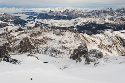 Skiers descend from the top of Marmolada in the Dolomites, Italy, Europe by Alex Treadway