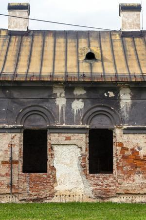 Facade of Old Abandoned House with Dark Windows in Slovakia by alexabelov