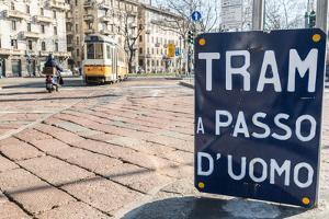An old sign in Italian that says Trams go to Duomo, with a traditional Milanese tram in the backgro by Alexandre Rotenberg