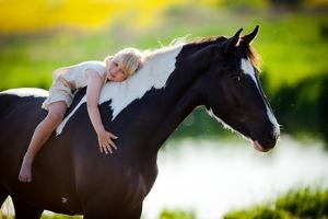 Child Sits On A Horse In Meadow Near Small River by Alexia Khruscheva