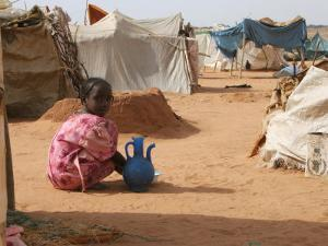 A Girl Washes Plates for Her Family in the North Darfur Refugee Camp of El Sallam October 4, 2006 by Alfred De Montesquiou