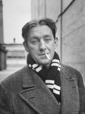 Actor Alec Guinness Dangling Cigarette from His Lips, on Movie Lot by Alfred Eisenstaedt