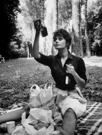 "Actress Sophia Loren Examining Contents of Bottle During Location Filming of ""Madame Sans Gene"""
