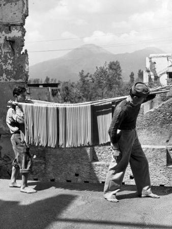 Boys Working in Pasta Factory Carry Rods of Pasta to Drying Rooms by Alfred Eisenstaedt
